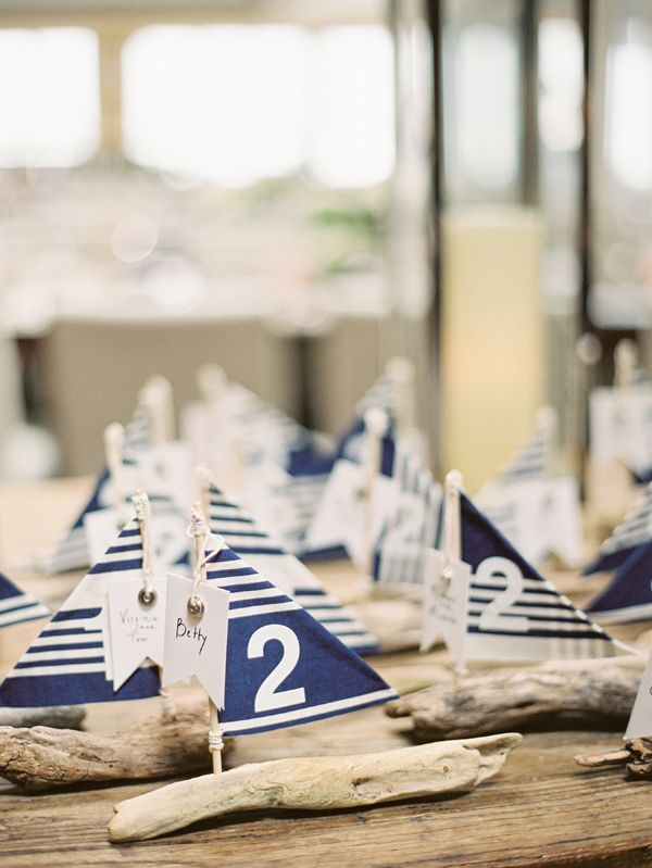 mini favors and escort cards of driftwood sailboats with navy and white decor and table numbers on them