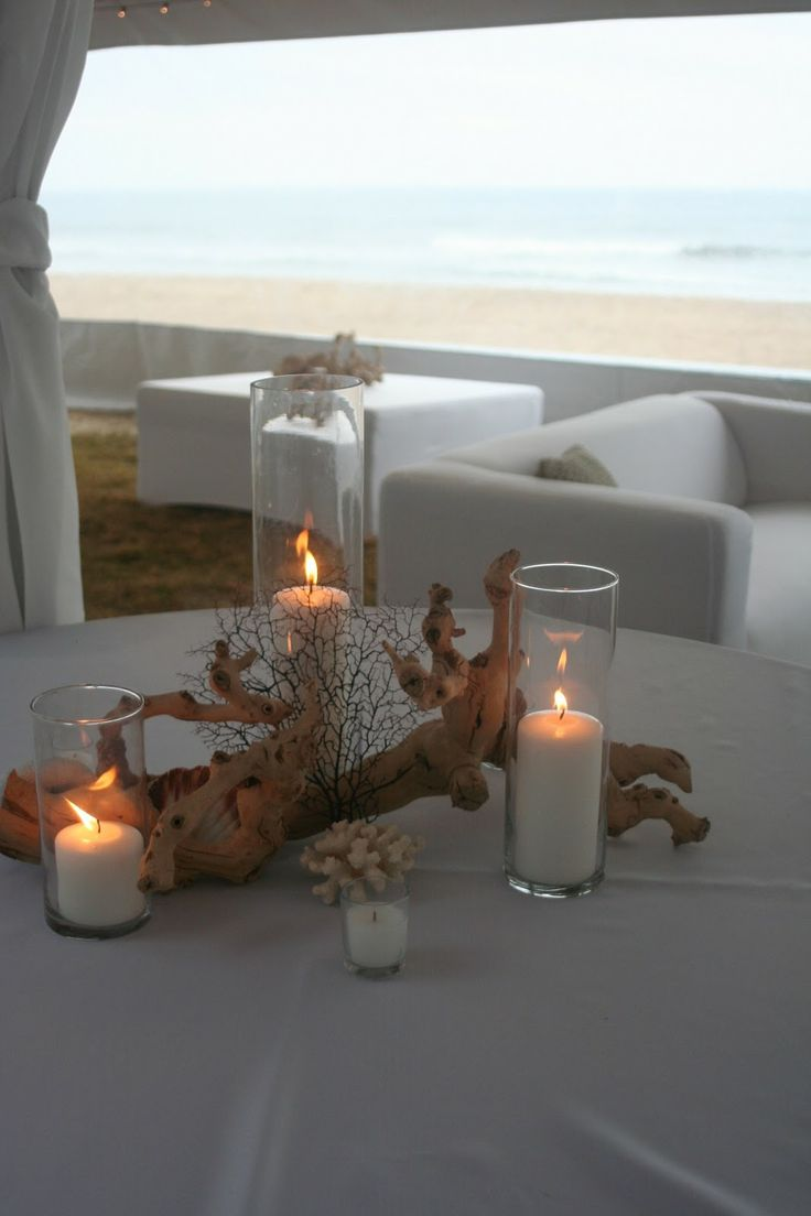 a beach wedding centerpiece of driftwood, candles and corals is easily DIYable and looks very beach appropriate