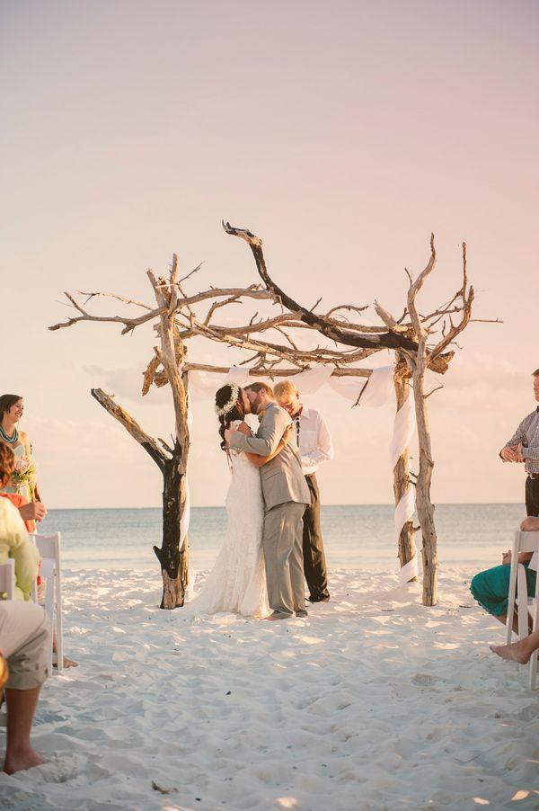 a driftwood wedding arch with white fabric is amazing for a coastal or beach wedding