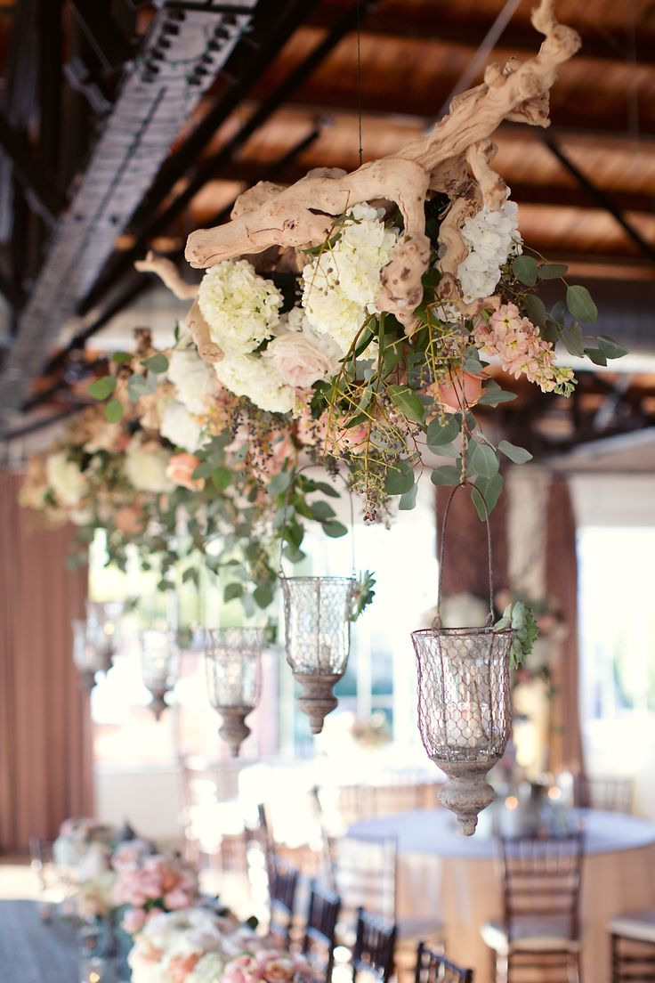 a driftwood wedding decoration of white and pastel blooms, greenery and candles hanging down is ideal for a beach or coastal wedding