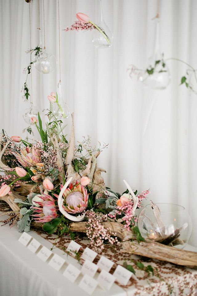 a lush beach wedding centerpiece of driftwood, pink tulips and king proteas, greenery and succulents