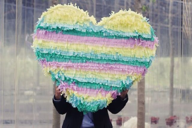 a colorful striped heart shaped pinata wedding guest book is a very bright and fun idea for a colorful wedding