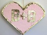a pink and gold heart-shaped with monograms is a lovely pinata and a cool alternative wedding guest book for a glam wedding