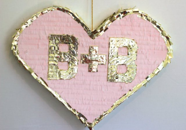 a pink and gold heart shaped with monograms is a lovely pinata and a cool alternative wedding guest book for a glam wedding