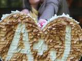 a tan and white fringe heart-shaped pinata as a creative wedding guest book, with monograms for more personalization is a lovely idea