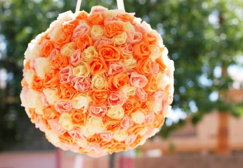 a bright orange, rust and white rose ball-shaped pinata wedding guest book is a colorful and fun idea for a modern wedding