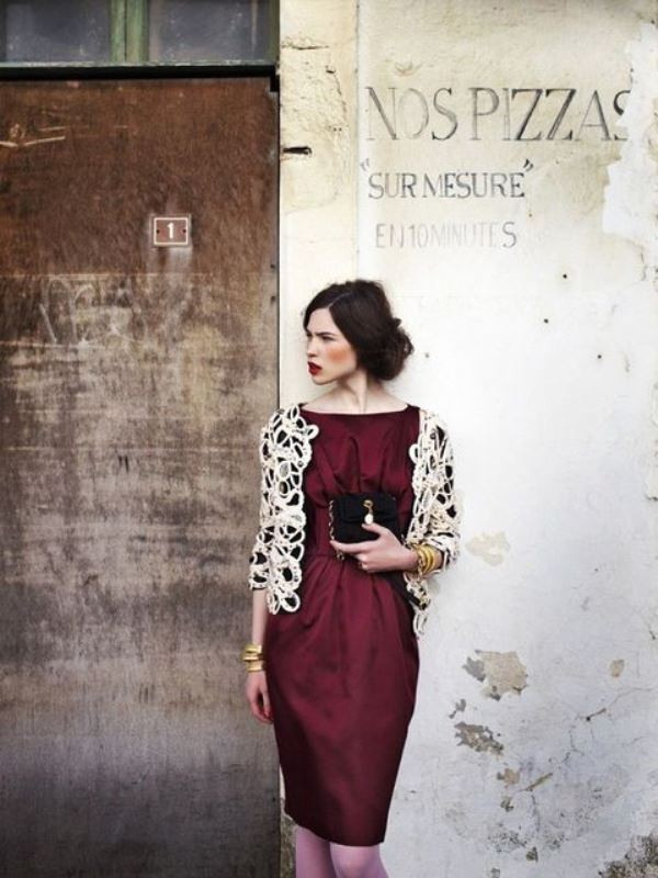 a burgundy knee dress with draping, a lace jacket with long sleeves and an embellished clutch