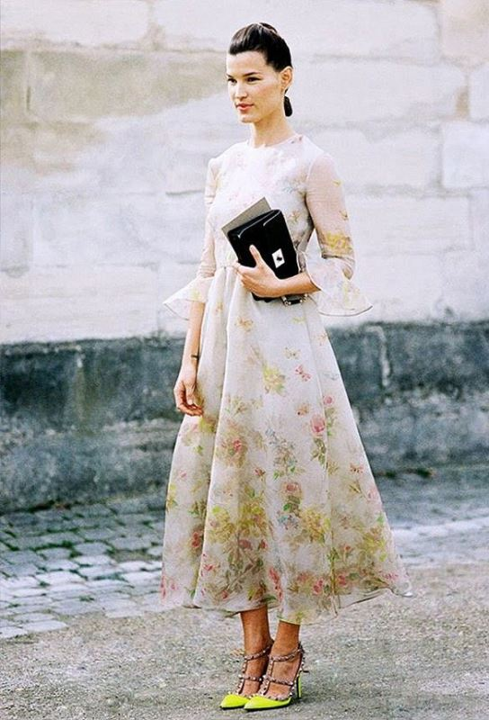 a floral midi dress with long sleeves, a high neckline, a black clutch and neon studded heels