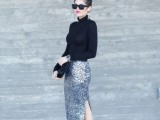 a silver midi skirt with a side slit, a black turtleneck, black shoes and a black clutch