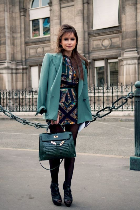 a colorful fitting mini dress, a green blazer, an emerald bag and black shoes with embellishments
