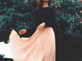 a black long sleeve top and a peachy pink pleated midi skirt for a simple and casual look
