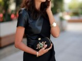 a black mini dress of leather and suede, with an asymmetrical skirt, an embellished snake clutch