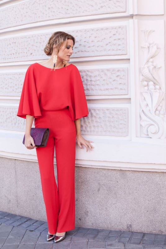 a red jumpsuit with a bateau neckline, long sleeves, silver heels, a purple clutch and statement earrings