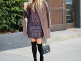 a printed purple over the knee dress, a brown coat, a grey bag and black boots