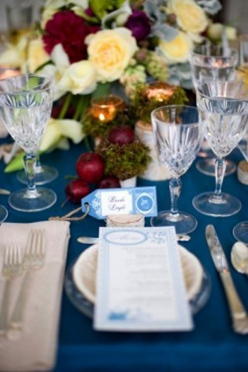 a blue winter wedding tablescape with red and white blooms, apples, blue cards and neutral napkins and menus