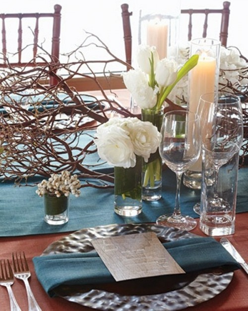 a winter wedding tablescape with a blue fabric table runner, napkins, a hammered charger, white blooms and a branch decoration