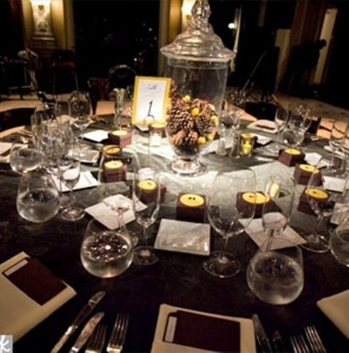 a brown winter tablescape with brown candles and pinecones and candles in a jar and a brown tablecloth