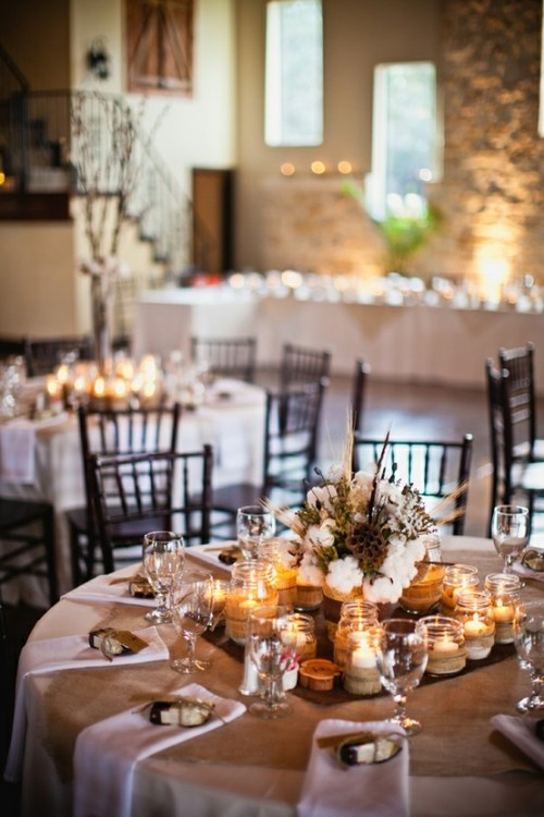 a rustic winter table in neutrals, with candles in jars, white napkins, a winter centerpiece of cotton, wheat, dried blooms