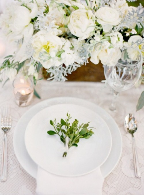 a white winter tablescape with white blooms, pale miller, mercury glass candleholders and greenery on each place setting