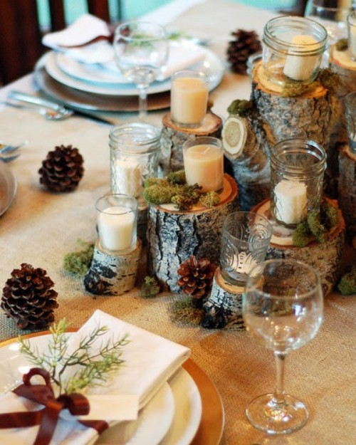 a rustic winter tablescape with stumps, pinecones, candles, gold chargers and moss
