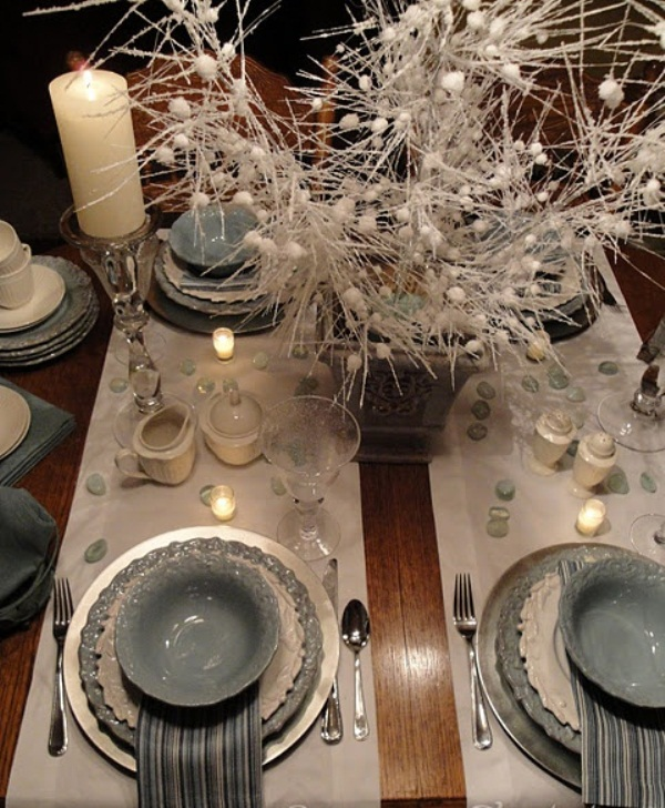 a grey and white winter wedding tablescape with grey and white porcelain, pebbles, candles, bead arrangement in a vase