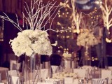 a white and silver winter tablescape with silver candleholders, a tall clear vase with branches and white blooms