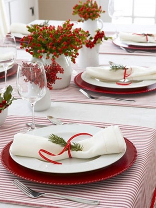 a red and white winter wedding tablescape  with red chargers, striped placemats, berries and greenery arrangements in white vases