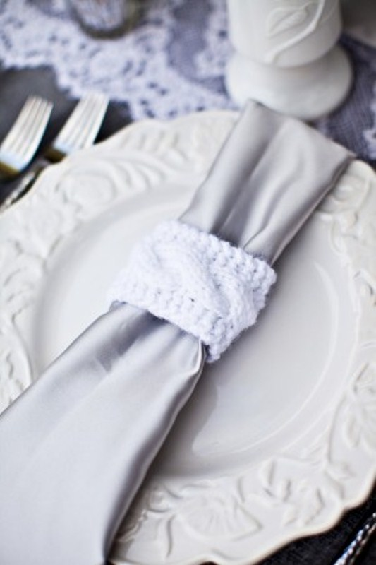 a silver and white tablescape with white porcelain with a silver napkin with knit napkin rings, lace runners