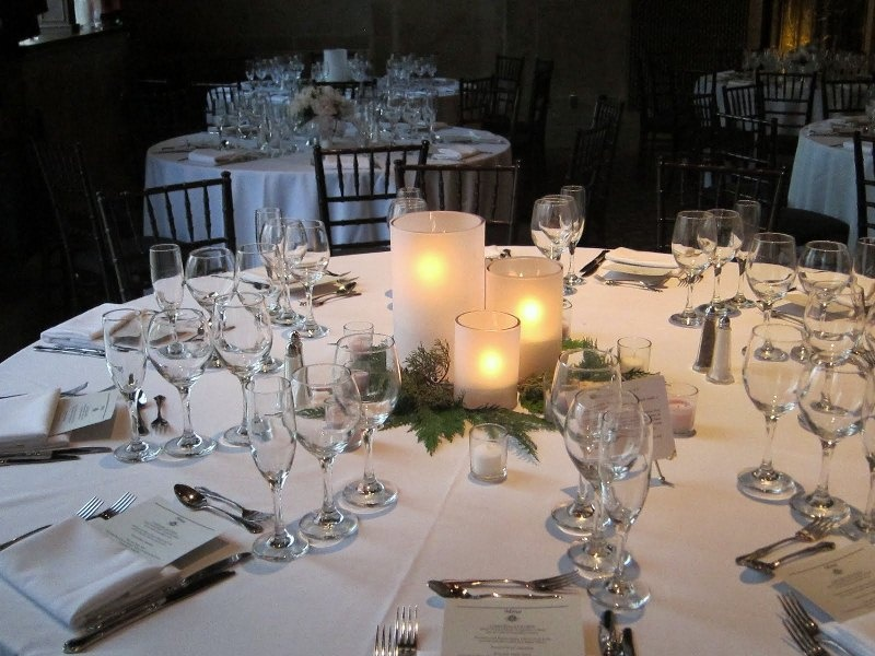 a winter wedding tablescape with candles with evergreens, neutral menus and white napkins is timelessly elegant