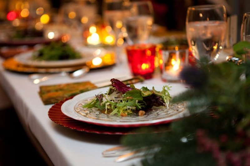 a green and red winter wedding table with lots of lights and candles in candleholders, evergreens and silver cutlery