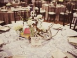 a winter wedding tablescape with books, antlers, cotton branches, some white blooms in glasses