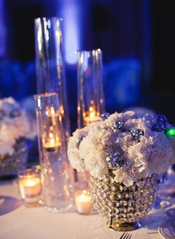 white blooms with crystals in a shiny vase, candles in vases and lots of shiny elements for a glam winter wedding table