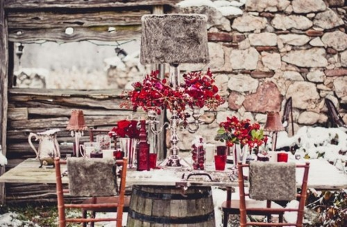 a taupe and red winter wedding tablescape with red blooms, pink lamps, red glasses and vases and silver cutlery