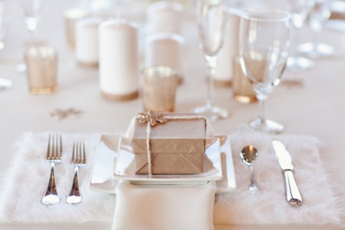 a neutral winter wedding table with candles, metallic candleholders, silver cutlery and fluffy placemats