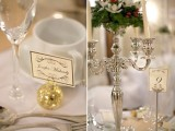 an elegant winter wedding tablescape with shiny ornaments, a silver candelabra with evergreens, berries and white blooms