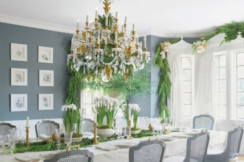 a winter wedding tablescape done with lots of evergreens, candles, blooms in pots, a large crystal chandelier with candles