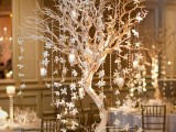 a white winter wedding table with a tree centerpiece with hanging crystals and candles, a neutral table number and porcelain