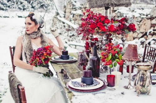 a bright winter wedding table done in purple, taupe, red and with metallic candleholders, vases and lamps