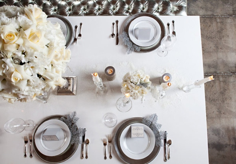an elegant neutral winter wedding tablescape with neutral blooms, candles, sivler cutlery and chargers, frozen snowflakes and foliage