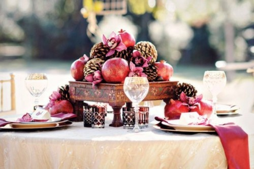 a winter wedding tablescape with red glasses, napkins, pomegranates and pinecones and red napkins