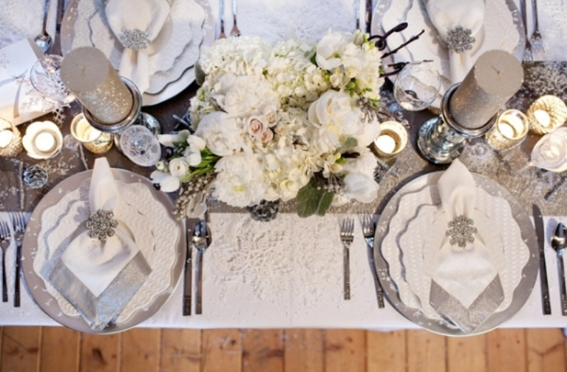 a silver, grey and white winter wedding table setting with grey sparkling candles, chargers, a shiny runner, white blooms and silver cutlery