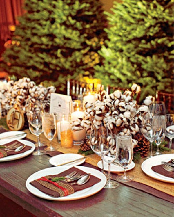 a rustic winter wedding tablescape with a burlap runner, cotton centerpieces, brown pockets, candles and simple cutlery