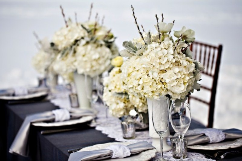 stylish black, white and silver winter wedding tablescape with white floral centerpieces, sivler napkins with white napkin rings, mercury glass candleholders and a black tablecloth