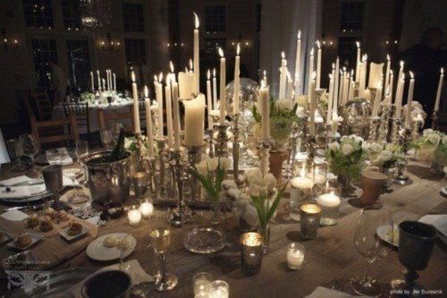 a neutral wedding table setting with a large candle centerpiece, neutral floral centerpieces, silver candleholders and glasses