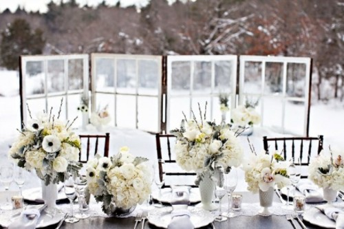 an all-neutral winter wedding table setting with lush white floral centerpieces, white porcelain and neutral napkins plus silver cutlery