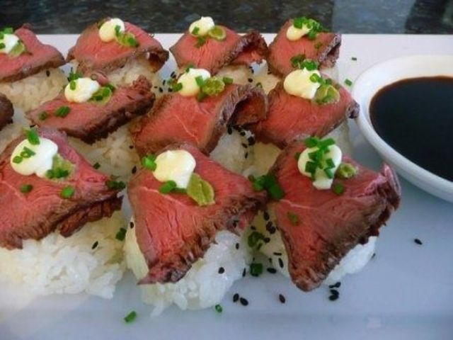 rice, beef slices and some cream and herbs on top plus soy sauce for a creative Japanese inspired appetizer