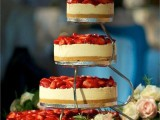 an assortment of classic cheesecakes topped with fresh strawberries on stands is a trendy idea