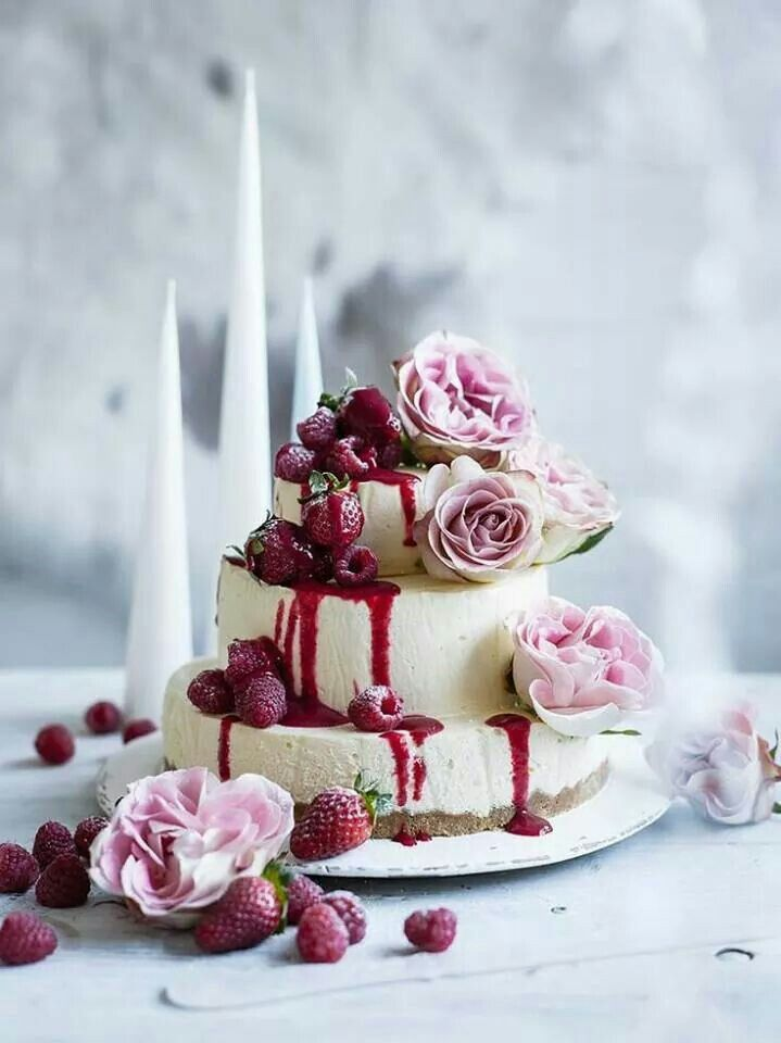 a three tiered white chocolate cheesecake with fresh raspberries and strawberries, pink roses is a refined idea