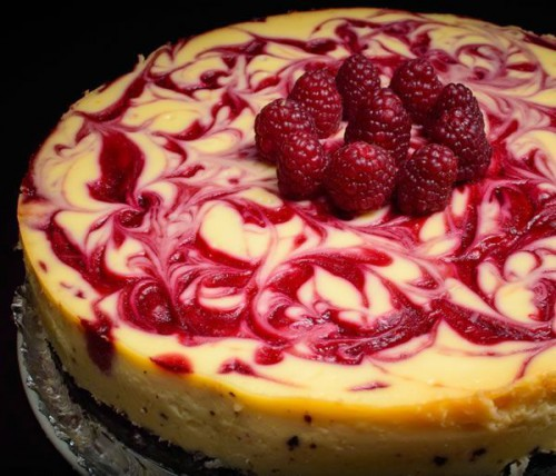 a swirl raspberry wedding cheesecake topped with fresh raspberries is a crowd-pleasing idea that tastes amazing