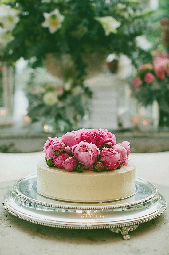 a white chocolate covered wedding cheesecake topped with fresh pink peonies